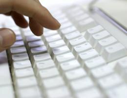 Hand typing at a keyboard