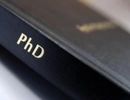A photograph of a hard bound PhD thesis with black cover